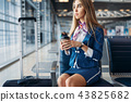 Stewardess with coffee on seat in waiting area 43825682