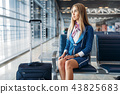 Stewardess with suitcase sitting in waiting area 43825683