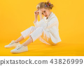 A teenage girl in white clothes sits stretching her legs forward on a yellow background. 43826999