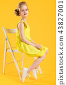 A girl is sitting on a white chair on a yellow background. 43827001