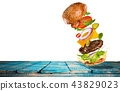 Big tasty burger with flying ingredients. 43829023
