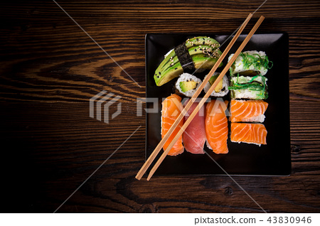 Various kinds of sushi served on wooden table. 43830946