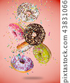 Tasty doughnuts in motion falling on pastel red background. 43831066