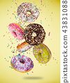 Tasty doughnuts in motion falling on pastel yellow background. 43831088