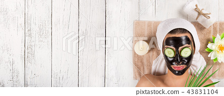 Portrait of young healthy woman with black peel face mask. 43831104