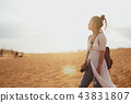 Woman exploring the desert, sandy beach with bag. 43831807