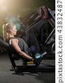 Sportive woman using weights press machine for legs. Gym. 43832487