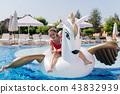 Delighted joyful woman swimming on an air unicorn 43832939