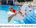 Joyful mother and daughter having fun on the air unicorn 43832953
