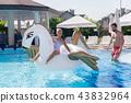Joyful happy girl swimming on an air unicorn 43832964