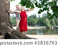 Emotional pensioner putting her hands up while standing with husband 43836763
