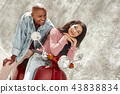 Active Lifestyle. Young diverse couple sitting on bike on the city street smiling relaxed 43838834