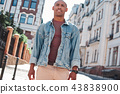 Confidence. Young guy walking on city street looking forward motivated 43838900