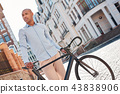 Pastime. Young guy walking on city street with bicycle looking aside thoughtful 43838906