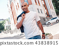 City walk. Young man walking on the city street carrying jacket looking forward motivated 43838915