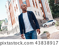 Outdoors leisure. Young man walking on the city street looking aside smiling curious 43838917