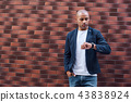 Time management. Young guy standing on wall looking at watch concerned 43838924