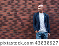 Creative thinking. Young guy standing leaning on wall smiling happy 43838927