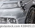 Detail on car front covered in soap foam 43840513