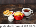 Baked omelet with golden crust in bowl with tea 43843074