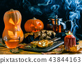 Halloween photo of table with pumpkin, biscuit, burning candle 43844163
