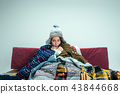The young woman with Flue Sitting on Sofa at Home. Healthcare Concepts. 43844668
