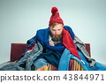 Bearded Man with Flue Sitting on Sofa at Home. Healthcare Concepts. 43844971