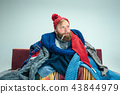 Bearded Man with Flue Sitting on Sofa at Home. Healthcare Concepts. 43844979