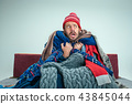Bearded Man with Flue Sitting on Sofa at Home. Healthcare Concepts. 43845044