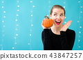Young woman holding a pumpkin 43847257