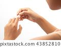 Woman injured finger and using bandage. 43852810