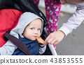 Mom feeding baby boy with bread crust outdoor. Child sitting in stroller during walk and tasting 43853555