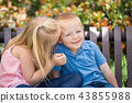 Affectionate Sister and Brother On a Park Bench 43855988