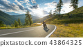 Motorcycle driver riding in Alpine highway, Nockalmstrasse, Austria, Europe. 43864325