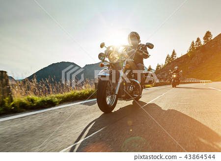 Motorcycle drivers riding in Alpine highway on famous Hochalpenstrasse, Austria, Europe. 43864544