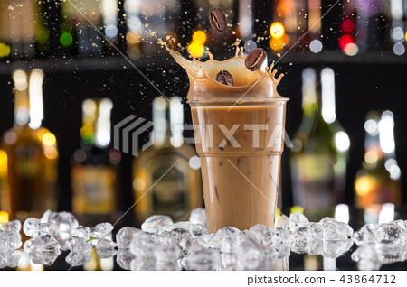 Cold coffee drink with ice, beans and splash. 43864712