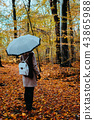 Female with rotate white umbrella in the autumnal golden colored forest path 43865988