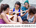 Woman plying guitar with her friends 43868233