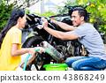 Couple washing motorcycle 43868249