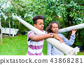 Brother and sister carrying pole in park 43868281