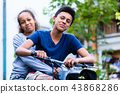 Smiling sister sitting with his brother riding an old bike 43868286