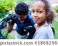 Portrait ofsmiling girl with boy looking at bike 43868296