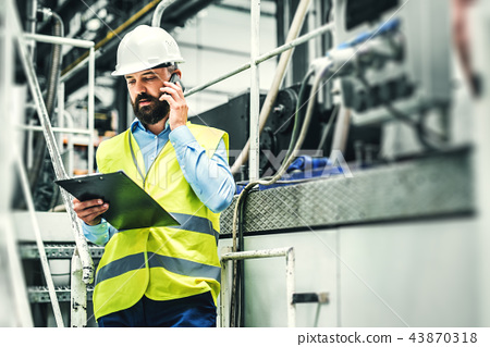 A portrait of an industrial man engineer with smartphone in a factory, working. 43870318