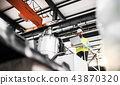 A low angle view of an industrial man engineer with laptop in a factory, working. 43870320