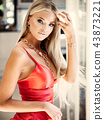 Young lady in red dress with luxury jewelry in modern interior 43873221
