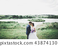 Perfect couple bride, groom posing and kissing in their wedding day 43874130