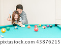 Couples are playing billiards in home 43876215