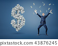 A happy businessman throws and catches money near a large dollar sign made of banknotes. 43876245