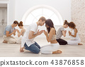 Group of people meditating indoors. Young family therapy 43876858