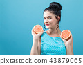 Happy young woman holding oranges 43879065